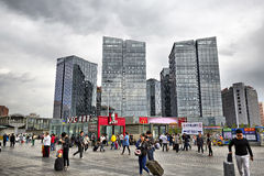 Commercial buildings and busy square with people. Office buildings and business square in the commercial area, stormy sky, Beijing city Royalty Free Stock Image