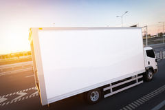 Commercial cargo delivery truck with blank white trailer driving on highway. Royalty Free Stock Image