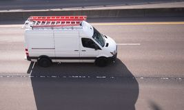 Commercial cargo mini van with long leaders on the roof running. On the road to point of service or place of construction business Royalty Free Stock Photo