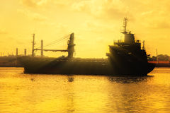 Commercial cargo ship at sunset Stock Photo