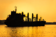 Commercial cargo ship at sunset Stock Images