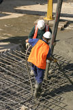 Commercial Cementing. Workers standing on thick steel mesh and pouring concrete through a large hose attached to a long extendable boom connected to a concrete Royalty Free Stock Photos