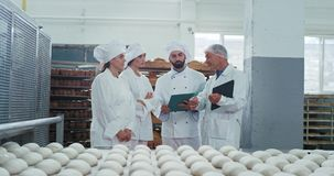 Commercial charismatic worker bakers and engineer have a meeting time at bakery industry modern factory interior , they. Make the plan of work.slow motions stock footage