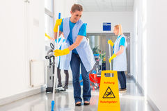Commercial cleaning brigade working. Mopping the floor royalty free stock image