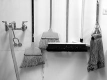 Commercial cleaning: brooms and mop. Commercial cleaning equipment: brooms and mop - black and white royalty free stock image