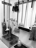 Commercial cleaning: brooms, mops, sink. Commercial cleaning equipment: brooms, mops, sink - black and white royalty free stock photo