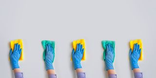 Commercial cleaning company. Employee hands in blue rubber protective glove. General or regular cleanup. Employee hands in blue rubber protective glove wiping stock image