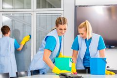Cleaning brigade working in office. Commercial cleaning crew ladies working as team in office royalty free stock images