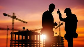 Commercial Construction Concept. With Silhouette of Two Workers Wearing Hard Hats and Construction Site in the Background stock photos