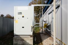 Gray commercial cooling unit standing outdoor on the ground near to the modern manufacturing building. Commercial cooling unit standing outdoor on the ground Royalty Free Stock Photo
