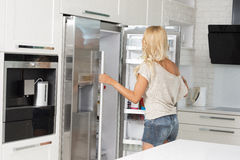 Commercial cute girl in front of refrigerator Stock Image