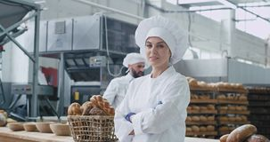 Commercial face of a amazing woman baker looking straight to the camera and smile cute background his colleague baker. Dancing and moving funny beside their stock footage