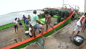 Commercial fishermen hauling catch fish from ship cold storage aboard. Dalahican, Lucena City, Philippines - December 29, 2017: Commercial fishermen hauling stock video footage