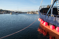 Commercial fishing boat at dock. Seattle,WA, USA Mar. 4, 2017: Blue and red commercial fishing boat with round red fenders reflecting in the waters of Fishermens Stock Images