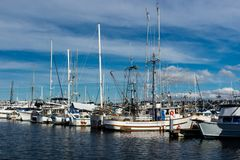 Commercial fishing boat docked at Fisherman`s Terminal in Seattle Washington. Bright blue sky stock photos