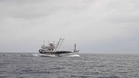 Fishing Boat in the Sea. A commercial fishing boat in the sea in slow motion stock video footage