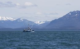 Commercial fishing boat in Southeast Alaska. Salmon fishing boat in Lynn Canal in Southeast Alaska with mountains in the background Royalty Free Stock Images