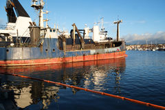 Commercial fishing boat and spill containment boom stock photo