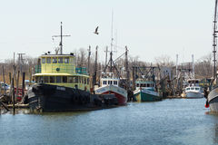 Commercial Fishing Boats in Belford, New Jersey. BELFORD, NEW JERSEY - April 11, 2017: Commercial fishing boats are docked at the Belford Seafood Cooperative royalty free stock photos