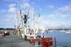 Commercial fishing boats by a wood dock stock images