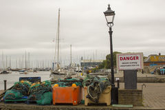 Commercial fishing nets stored in a pile beside a leaning street lamp on the quayside at Lymington Harbour in Hampshire on the sou Stock Photography