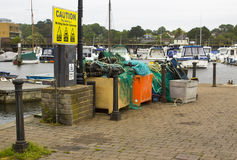 Commercial fishing tackle and nets piled on the quayside at the harbour in Lymington, Hampshire on the South Coast of England. Commercial fishing tackle and nets Stock Images