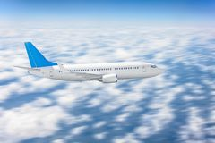Commercial flight airplane flies in the sky against a background of clouds. Motion blur effect.  stock photos