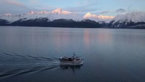 Commercial halibut longliner. Commercial fishing boat traveling across Alaska waters during sunset in the winter stock video footage