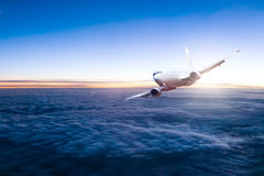 Commercial jet aeroplane flying above clouds Stock Photos