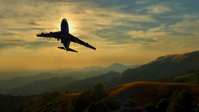 Commercial jet aeroplane maneuvering over mountain. Range Royalty Free Stock Photos