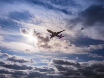 A commercial jet airliner partially silhouetted against the sun Royalty Free Stock Photos