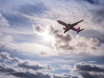 A commercial jet airliner partially silhouetted against the sun Royalty Free Stock Photo