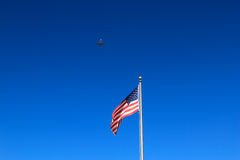 Commercial jet airplane flying in the sky over the American flag. Stock Photo