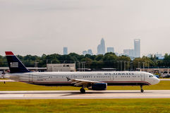 Commercial jet on an airport runway with city skyline in the bac Royalty Free Stock Image