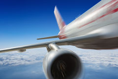 Commercial jet flies very fast in blue sky Royalty Free Stock Photography