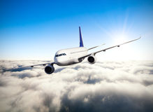 Commercial jet plane flying above clouds Royalty Free Stock Photos