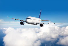 Commercial jet plane flying above clouds. In day light Stock Images