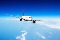 Commercial jet plane flying above clouds Stock Image