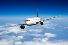 Commercial jet plane flying above clouds Royalty Free Stock Photography