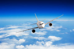 Commercial jet plane flying above clouds Stock Photography