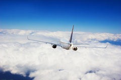 Commercial jet plane flying above clouds Stock Photos