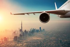 Commercial jet plane flying above Dubai city stock photography