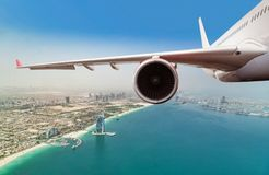 Commercial jet plane flying above Dubai city stock images