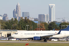 Commercial Jet on Runway with City Skyline Stock Image