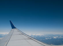 Commercial Jetliner Wing above Clouds and Mountain. The view out the window of a commercial aircraft. Clouds and mountains are visible below stock photos