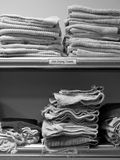 Commercial kitchen: dish drying towels. Commercial kitchen with dish drying towels on stainless steel shelf - black and white Stock Photo