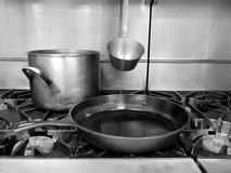 Commercial kitchen: stove top pot and pan. Commercial kitchen stove top with gas burners, cast iron frying pan, stainless steel pot and ladle - black and white Royalty Free Stock Photography