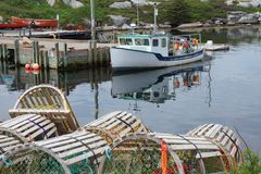 Wooden lobster traps and a fishing boat in Peggy`s Cove, Nova Scotia royalty free stock images
