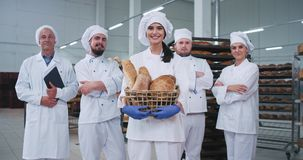 Commercial looking bakery main team bakers engineer in front of a beautiful lady with a basket of fresh bread looking. Straight to the camera and smile. 4k stock video