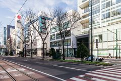 Commercial modern building with leafless trees on traffic island in Sapporo in Hokkaido, Japan Stock Photos